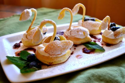Puff pastry swans with Chantilly cream and berries.
